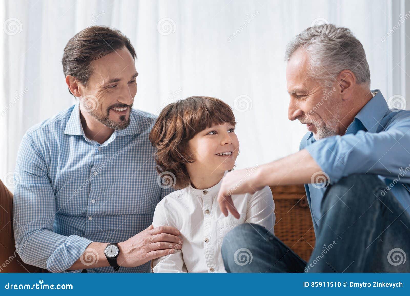 Όμορφος ευχαριστημένος παππούς που εξετάζει τον εγγονό του