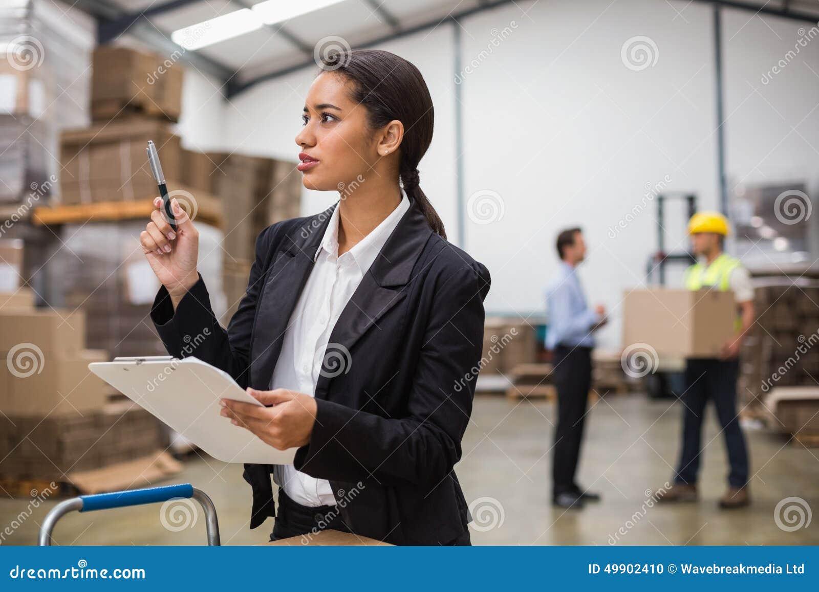 Όμορφος διευθυντής αποθηκών εμπορευμάτων που ελέγχει τον κατάλογο