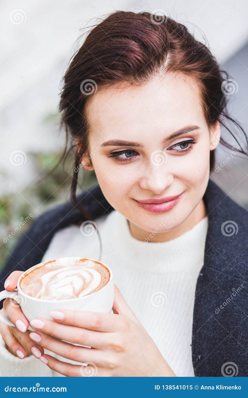 Όμορφος καφές cappuccino κατανάλωσης γυναικών brunette με τον αφρό στον καφέ οδών