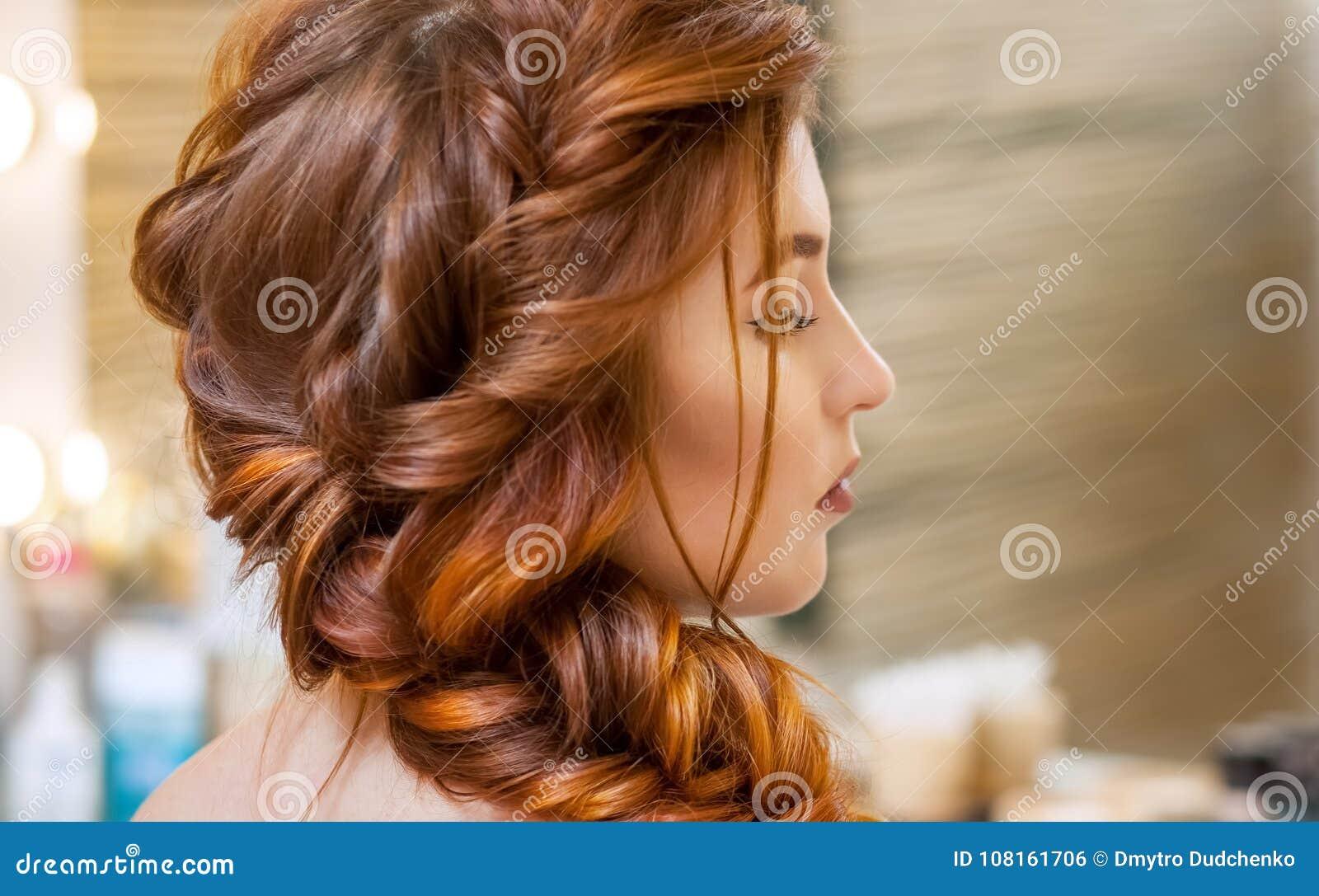 Όμορφος, με το μακρύ, κοκκινομάλλες τριχωτό κορίτσι, κομμωτής υφαίνει μια γαλλική πλεξούδα, σε ένα σαλόνι ομορφιάς