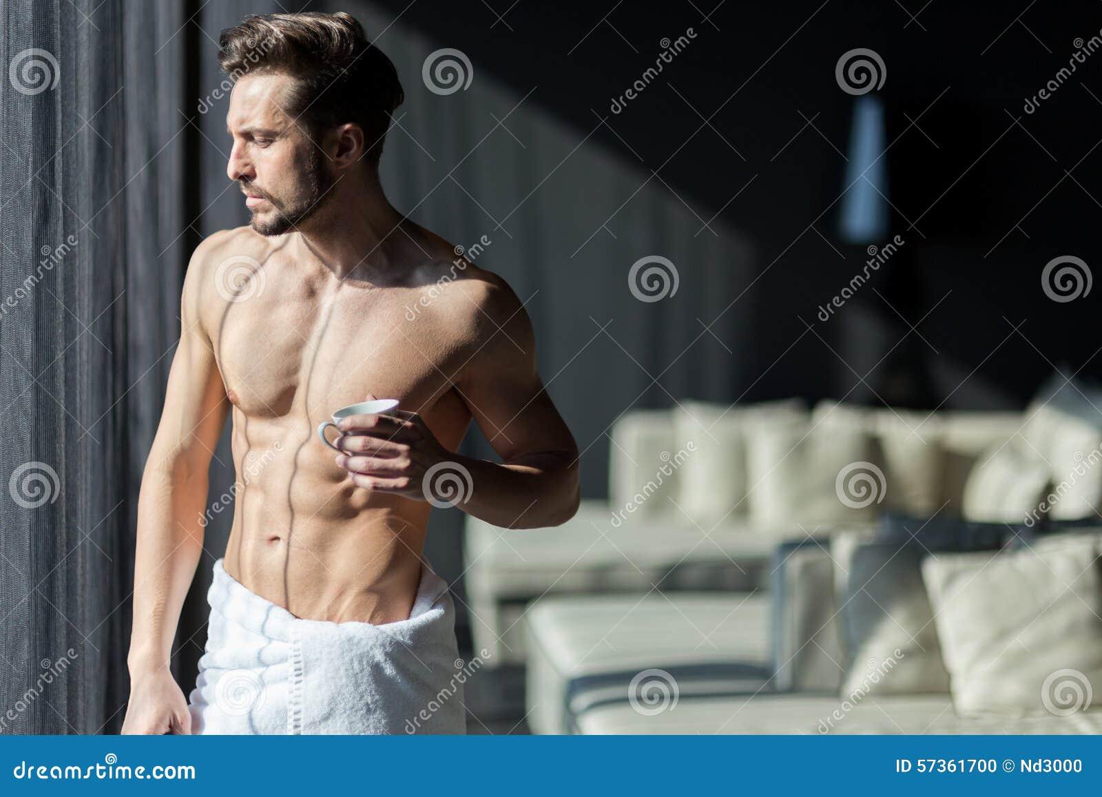 Όμορφος, μυϊκός, νεαρός άνδρας που πίνει τον καφέ πρωινού του σε ένα χ