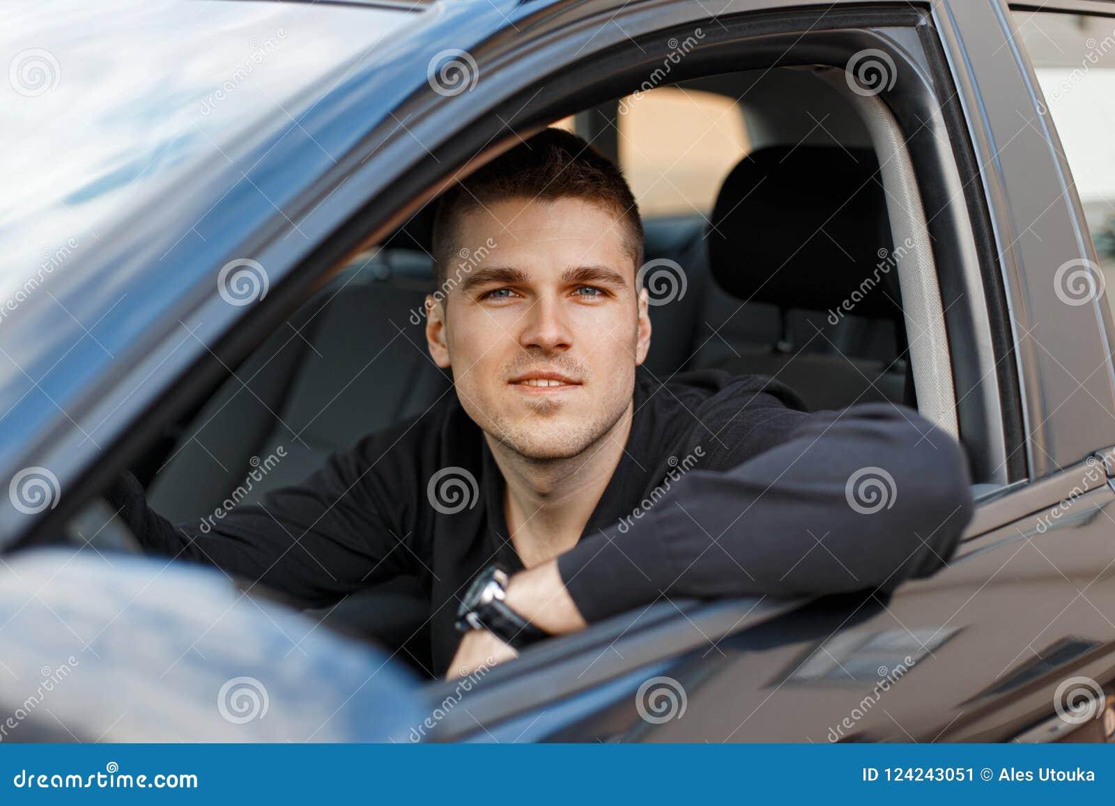 Όμορφος νέος αρσενικός οδηγός σε ένα μαύρο αυτοκίνητο