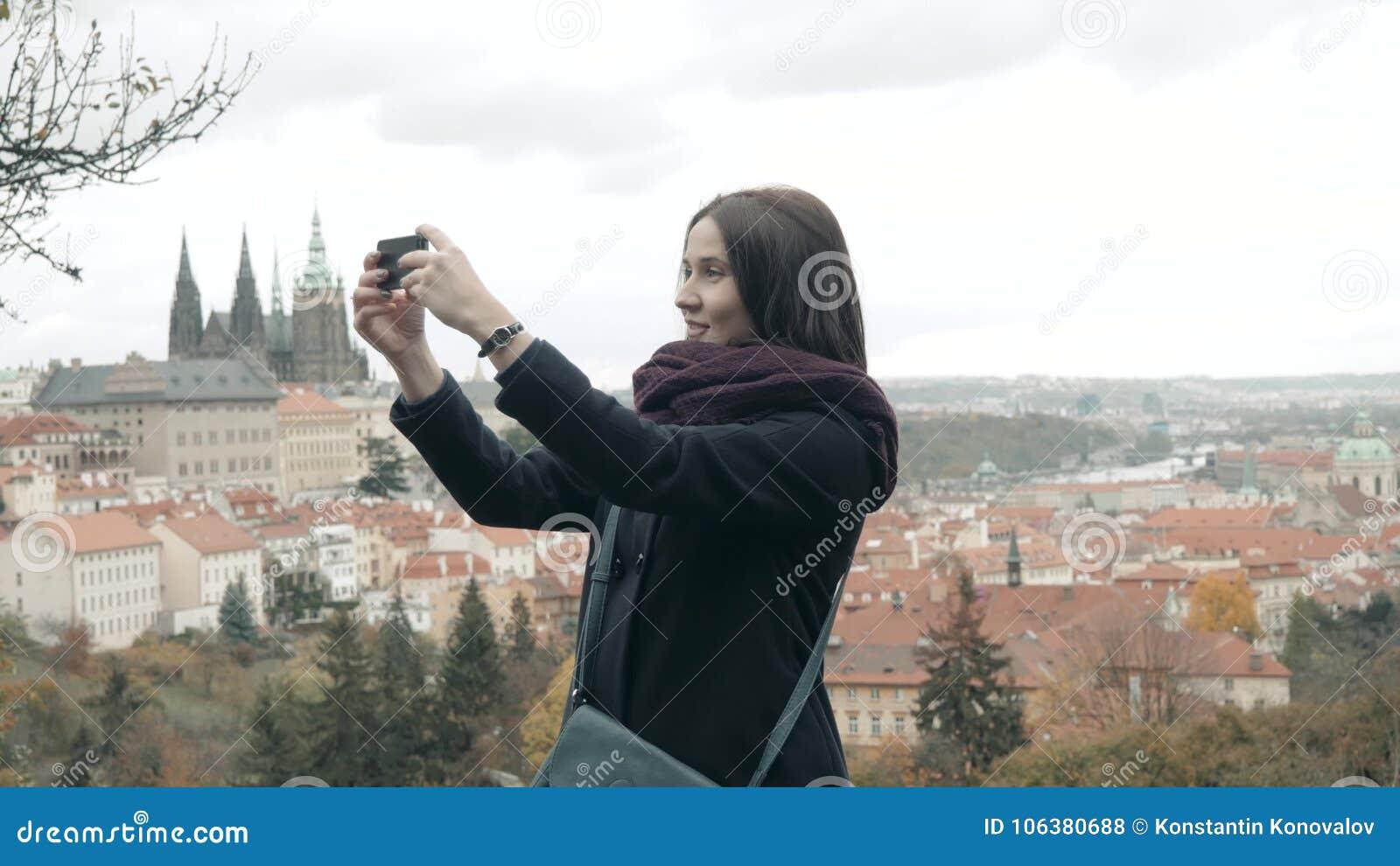 Όμορφος νέος τουρίστας γυναικών στην Πράγα, που κάνει Selfie ή που παίρνει τη φωτογραφία με το κινητό τηλέφωνό της, που ταξιδεύει
