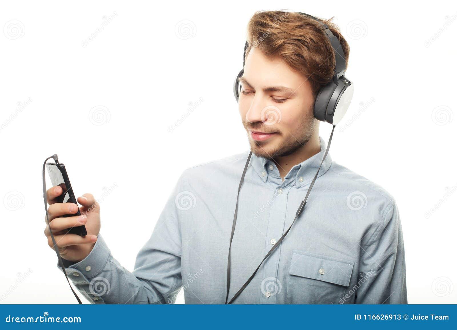 Όμορφος νεαρός άνδρας που φορά τα ακουστικά και που ακούει τη μουσική