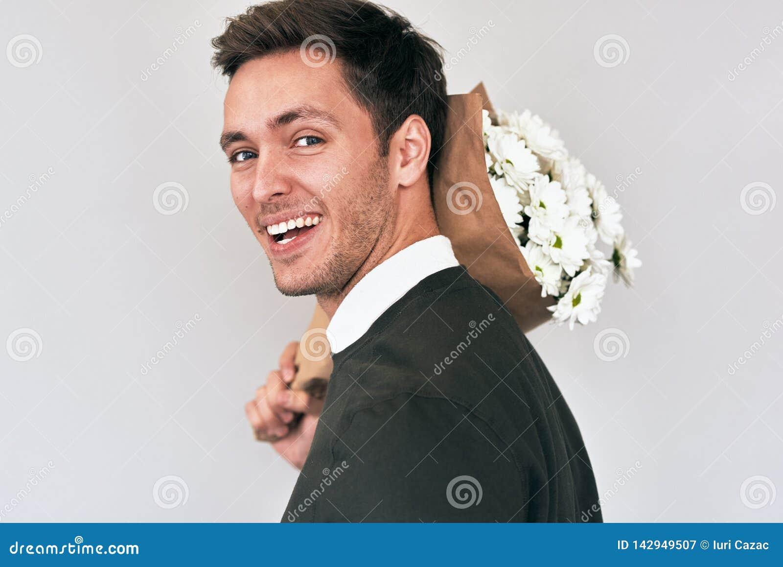 Όμορφος νεαρός άνδρας που χαμογελά και που παραδίδει μια ανθοδέσμη των άσπρων λουλουδιών Ελκυστικό αρσενικό πρότυπο με μια δέσμη