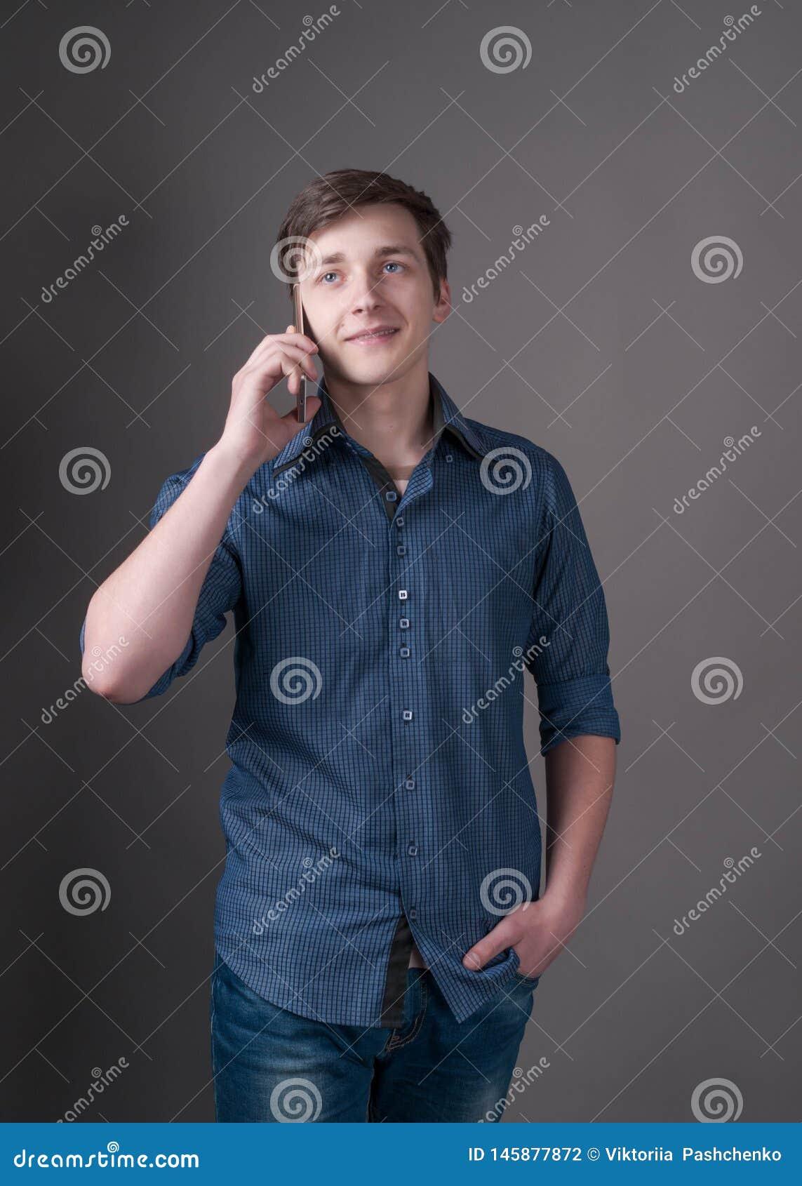 Όμορφος νεαρός άνδρας στο μπλε πουκάμισο που μιλά στο smartphone και που κοιτάζει μακριά στο γκρι