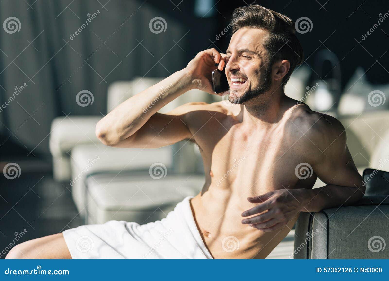 Όμορφος, νεαρός άνδρας που μιλά στο τηλέφωνο κυττάρων του το πρωί μέσα