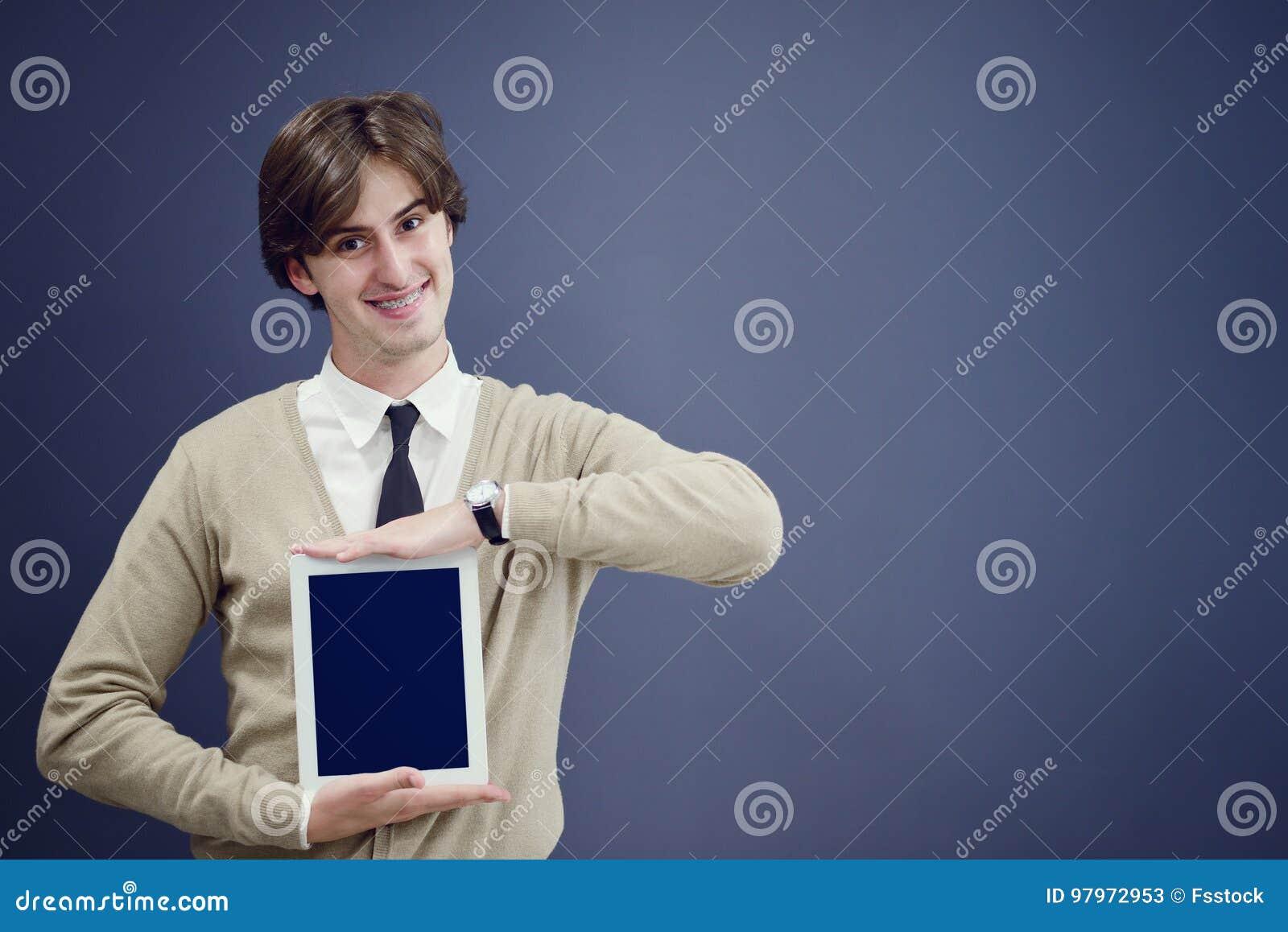 Όμορφος νεαρός άνδρας που παρουσιάζει κάτι σε μια ταμπλέτα, που απομονώνεται πέρα από το γκρίζο υπόβαθρο