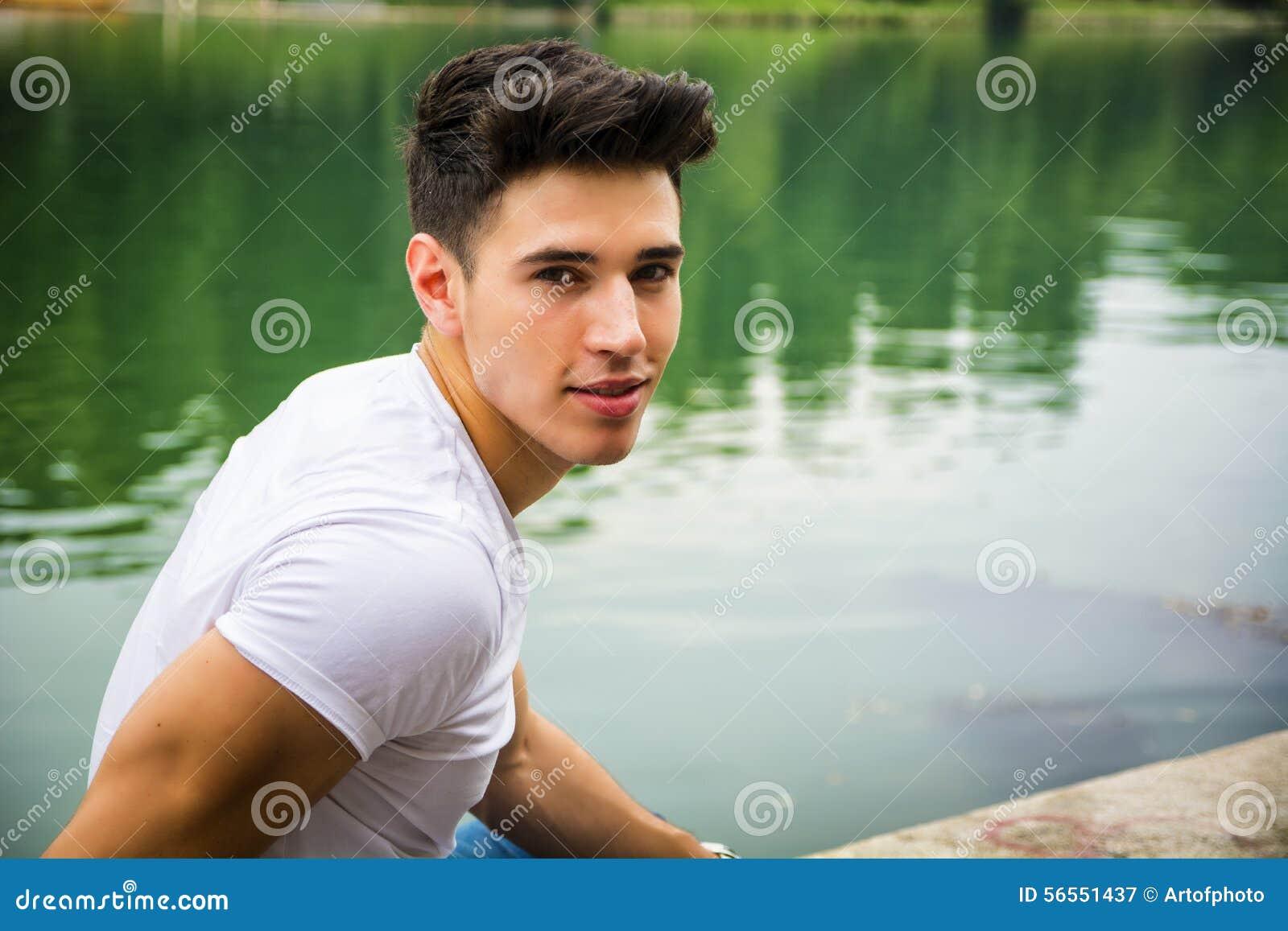 Download Όμορφος νεαρός άνδρας στην ακτή ή τον ποταμό μιας λίμνης Στοκ Εικόνα - εικόνα από αρσενικό, leisure: 56551437