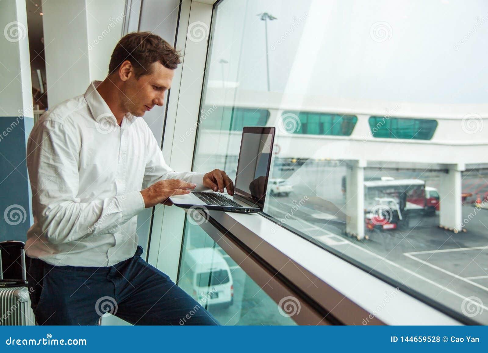 Όμορφος νεαρός την άνδρας που εργάζεται με το lap-top στον αερολιμένα κατ