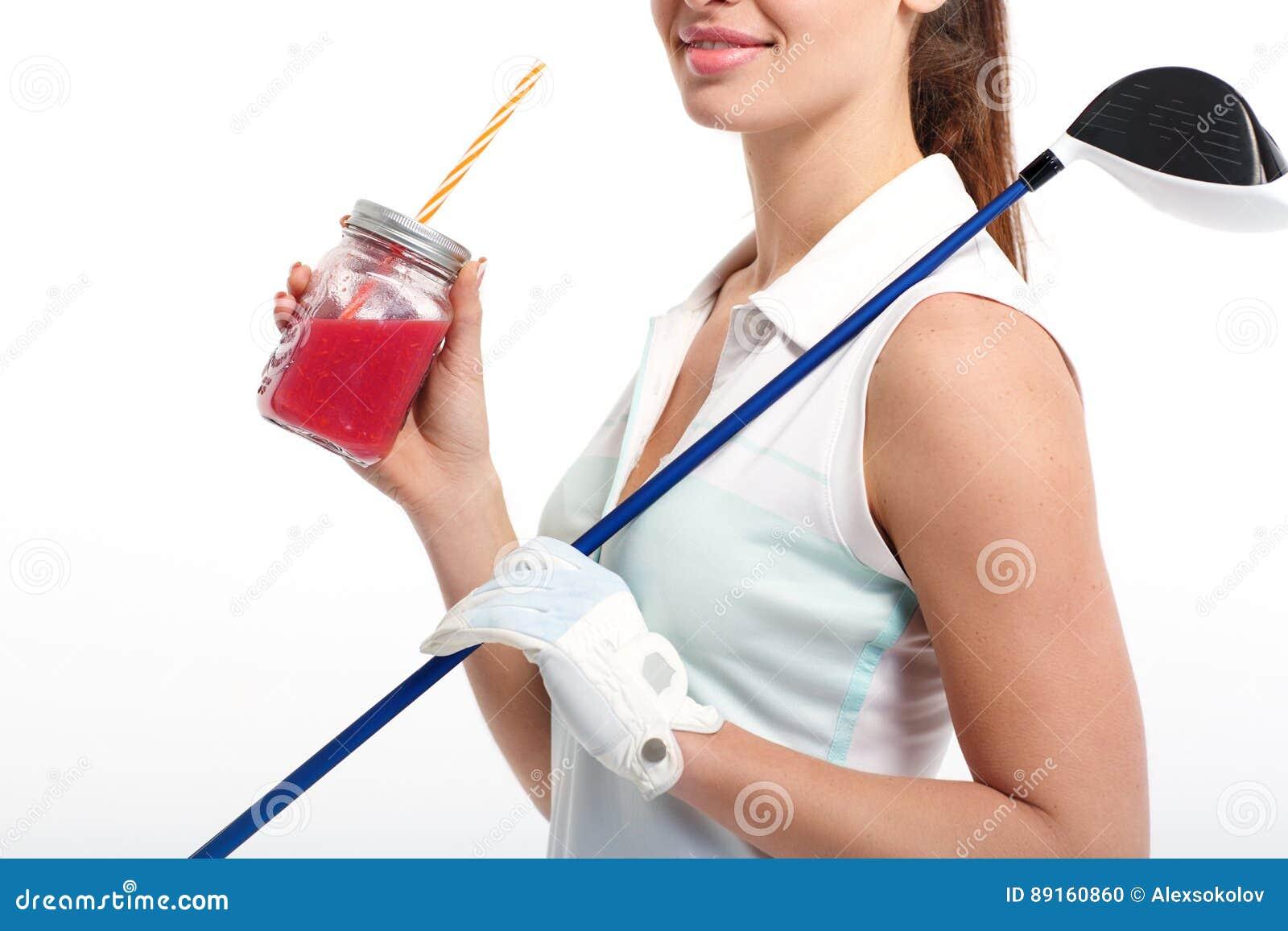 Όμορφος παίκτης γκολφ κοριτσιών με το βάζο του χυμού detox στο στούντιο
