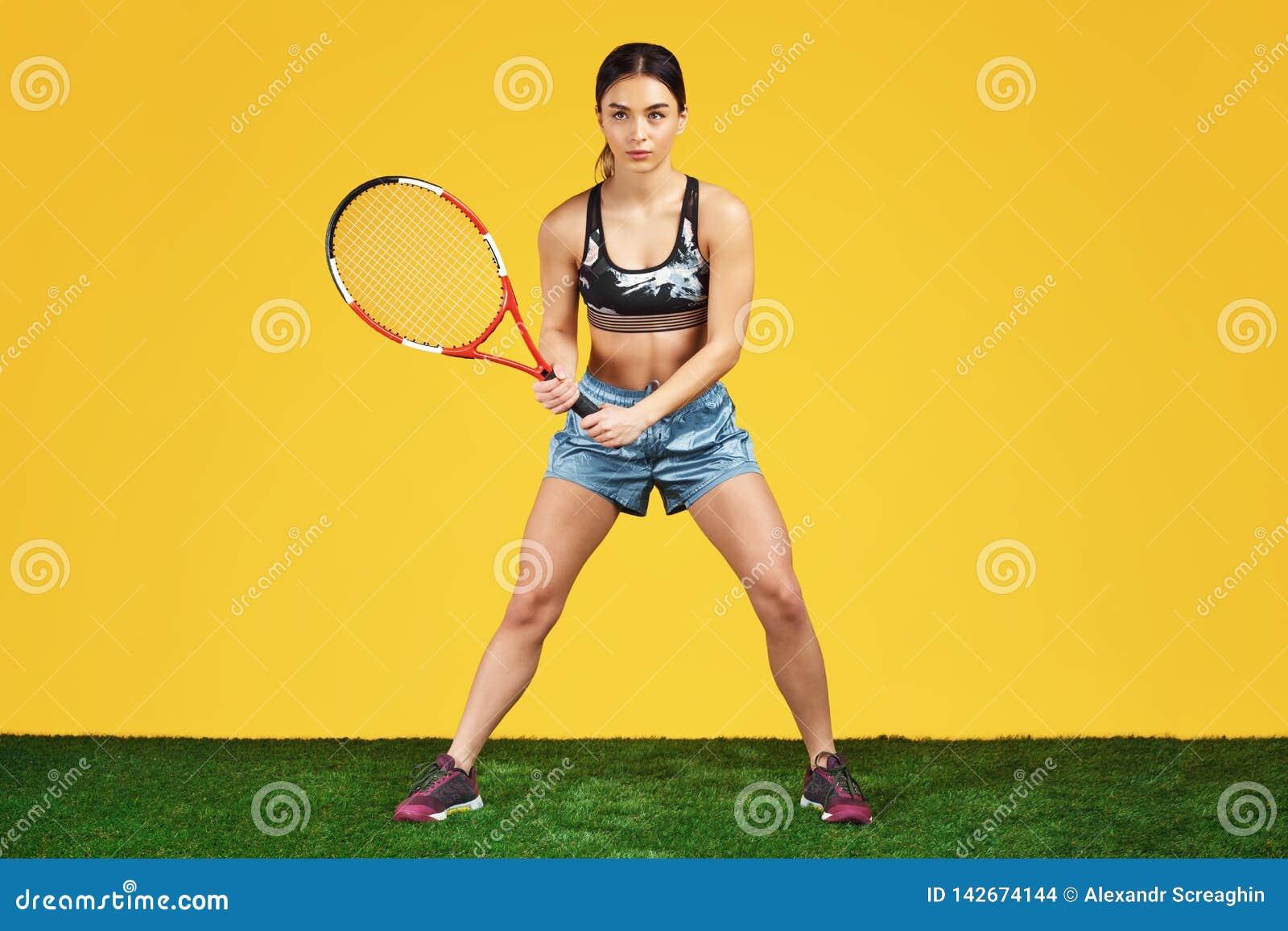Όμορφος φίλαθλος νέος τενίστας γυναικών έτοιμος πυροβοληθείς τη σφαίρα με την κόκκινη ρακέτα πέρα από το κίτρινο υπόβαθρο