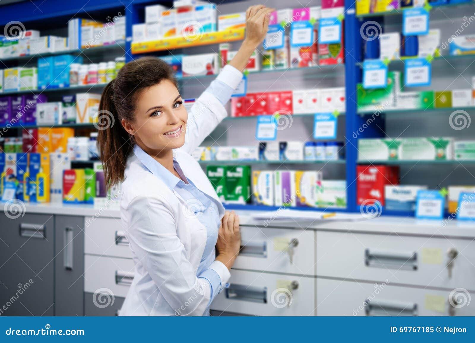 Όμορφος χαμογελώντας νέος φαρμακοποιός γυναικών που κάνει την εργασία του στο φαρμακείο