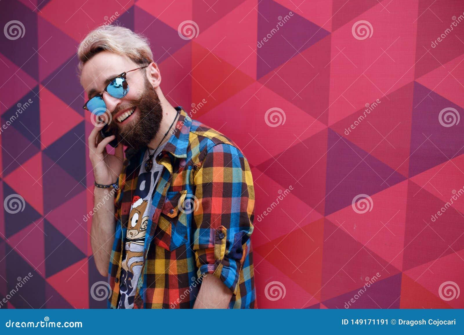 Όμορφος χαρισματικός νεαρός άνδρας που μιλά στο κινητό τηλέφωνο, σε ένα multicolore backgound