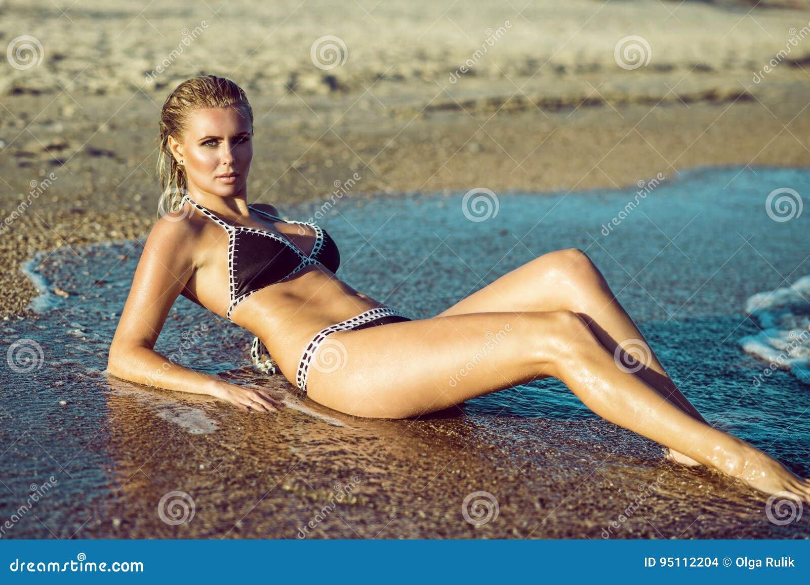 Όμορφος glam η ξανθή γυναίκα με το υγρό δέρμα και η τρίχα που βρίσκεται στην παραλία και που απολαμβάνει, τα μακριά πόδια της που
