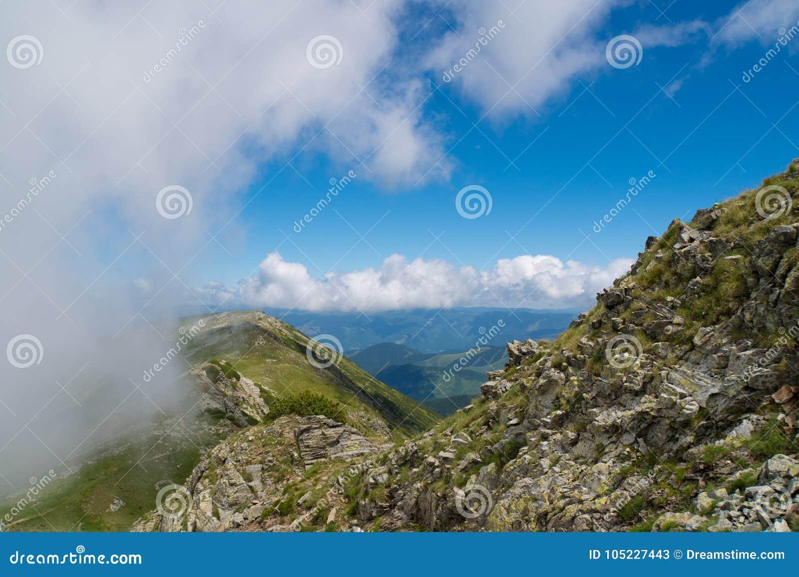 Όμορφο άγριο τοπίο με τα δύσκολα βουνά και έναν όμορφο θερινό ουρανό