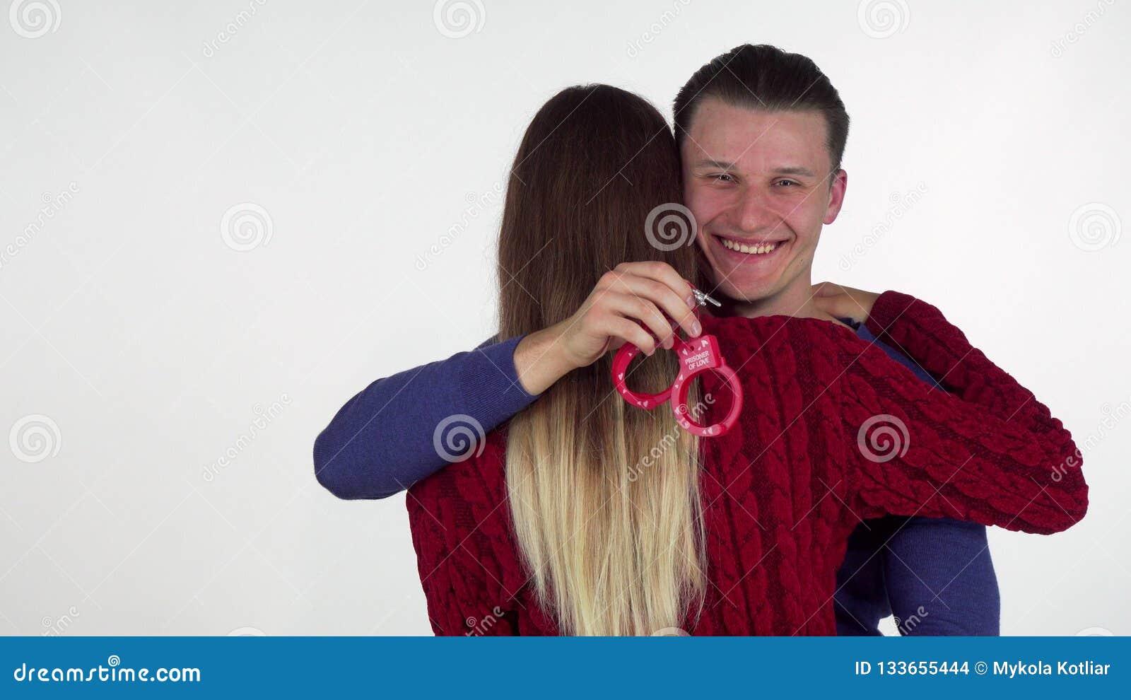 Όμορφο άτομο που αγκαλιάζει τη φίλη του, που κρατά τις χειροπέδες παιχνιδιών φύλων πίσω από την πίσω