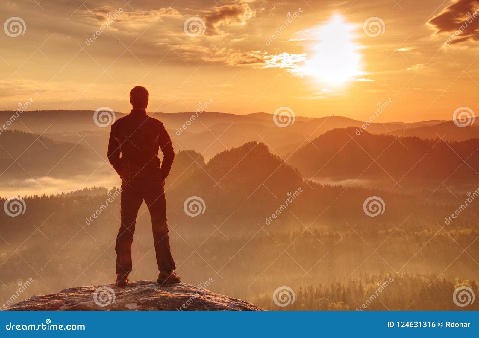 Όμορφο αθλητικό άτομο, ένας τουρίστας, παραμονή στο βράχο συνόδου κορυφής Άγρια υδρονέφωση