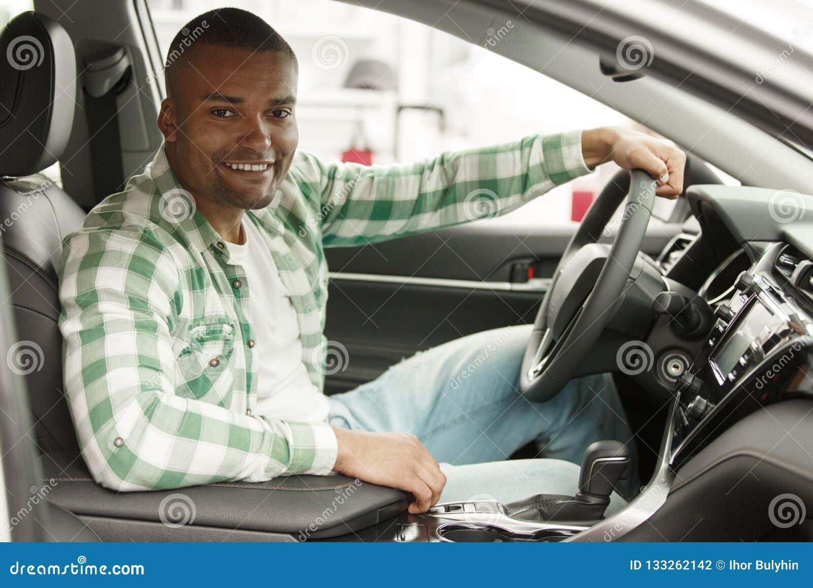 Όμορφο αφρικανικό άτομο που επιλέγει το νέο αυτοκίνητο στον αντιπρόσωπο