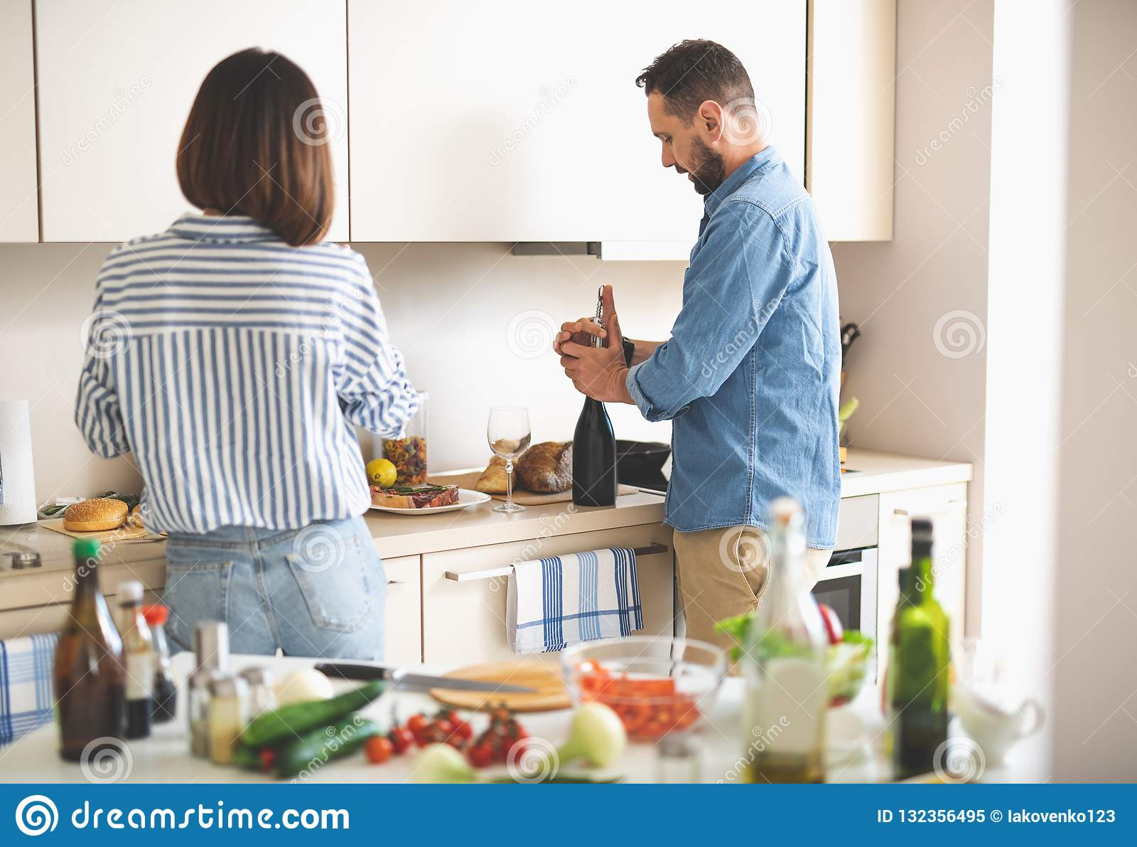 Όμορφο ζεύγος που προετοιμάζεται για το ρομαντικό γεύμα στην κουζίνα