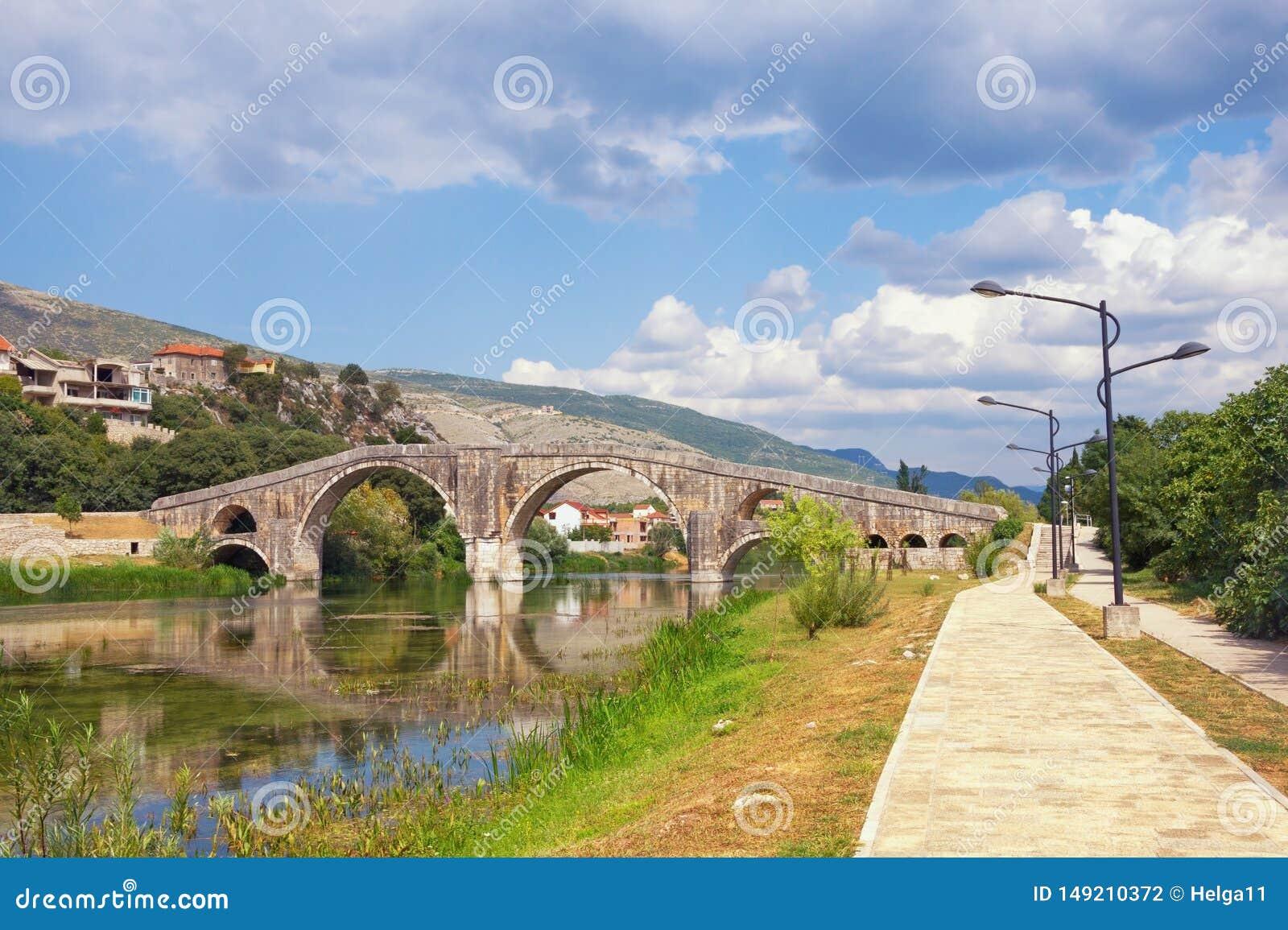 Όμορφο θερινό τοπίο με την παλαιά γέφυρα πετρών Βοσνία-Ερζεγοβίνη, άποψη του ποταμού Trebisnjica, ανάχωμα της πόλης Trebinje