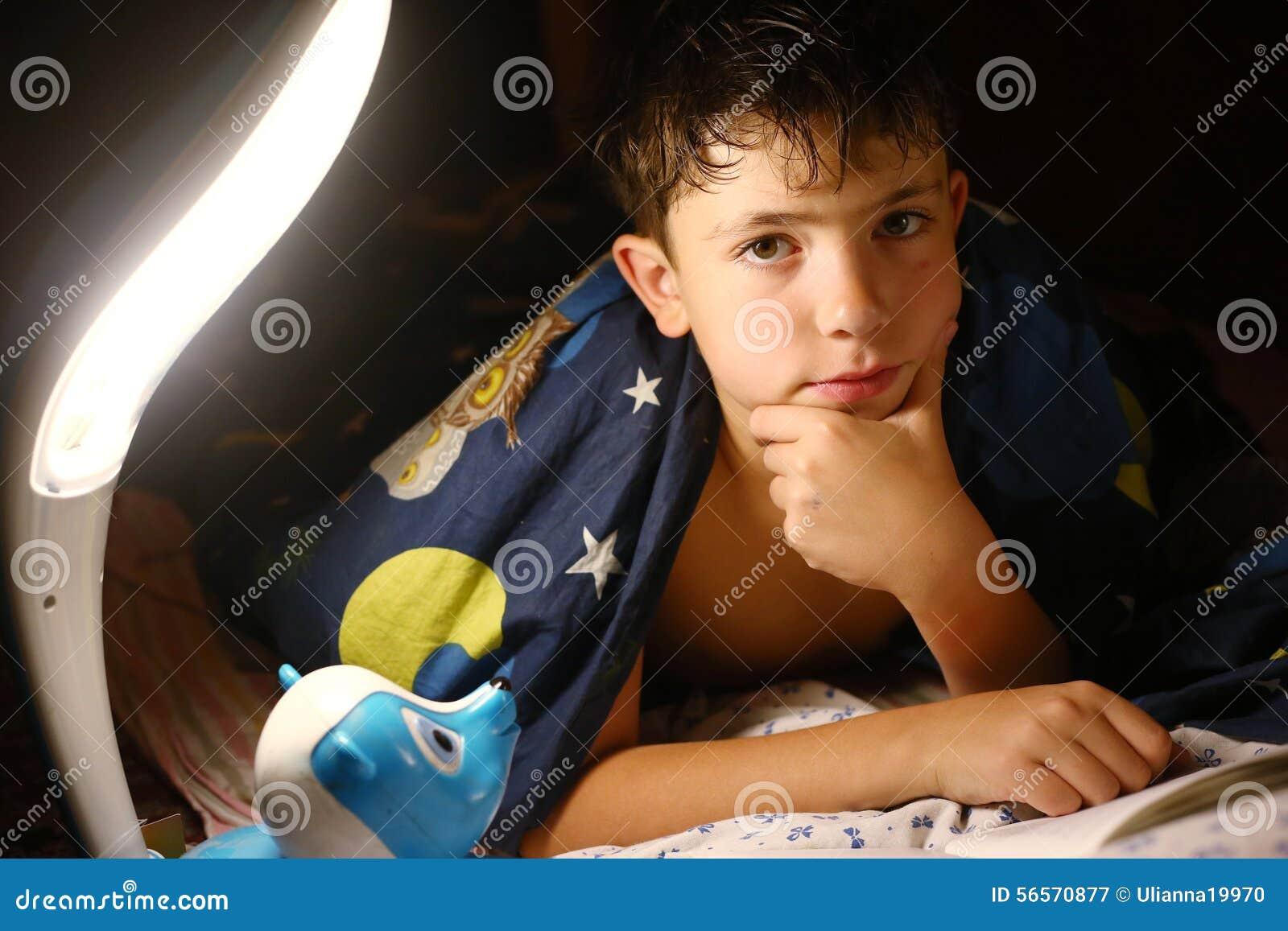Download Όμορφο διαβασμένο αγόρι βιβλίο Preteen με το λαμπτήρα πριν από τον ύπνο Στοκ Εικόνα - εικόνα από καυκάσιος, καλμένη: 56570877