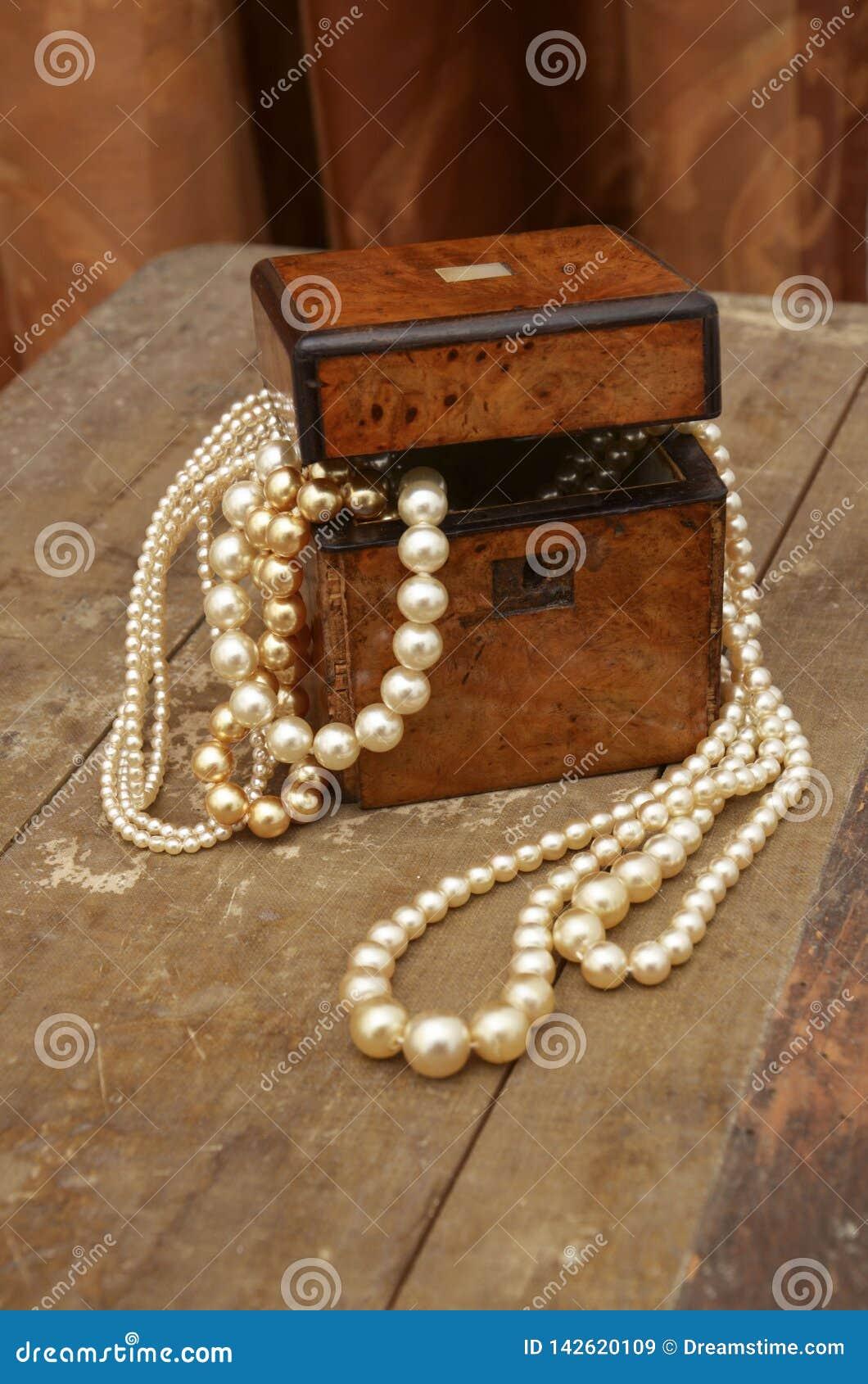 Όμορφο και καλό jewellerybox με τα μαργαριτάρια σε έναν παλαιό πίνακα