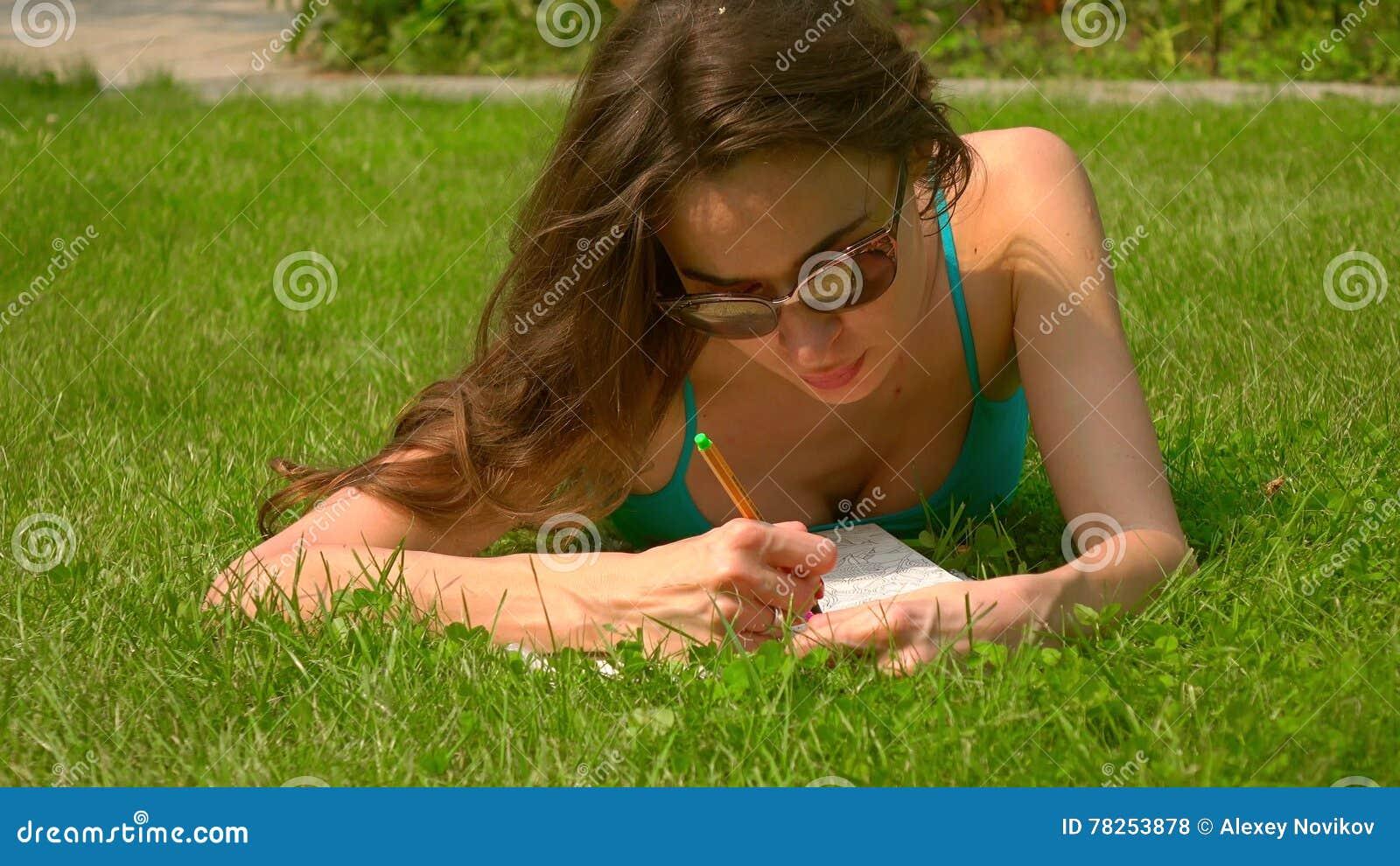 Όμορφο καυκάσιο κορίτσι brunette που βάζει στο χορτοτάπητα και τη colorizing εικόνα
