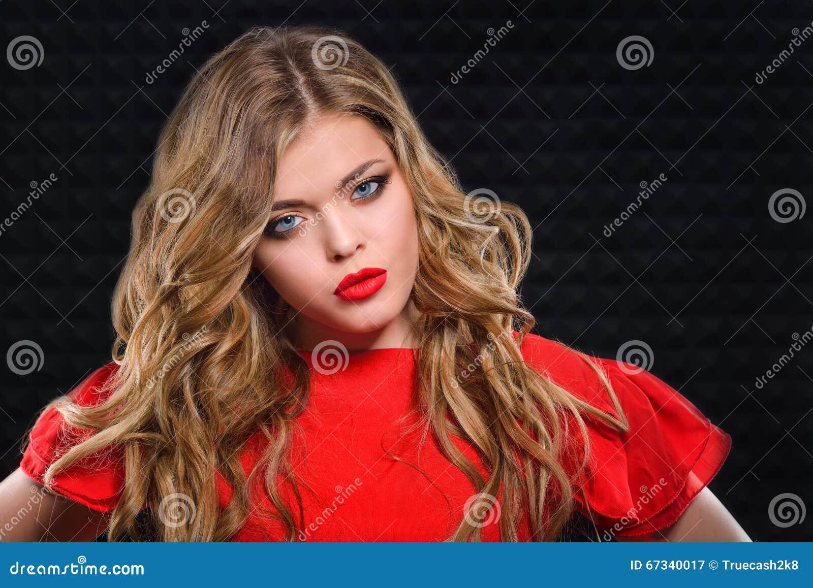 e0ba5b1a16f1 Όμορφο κορίτσι με τα κυματιστά ξανθά μαλλιά στο κόκκινο φόρεμα Στοκ ...