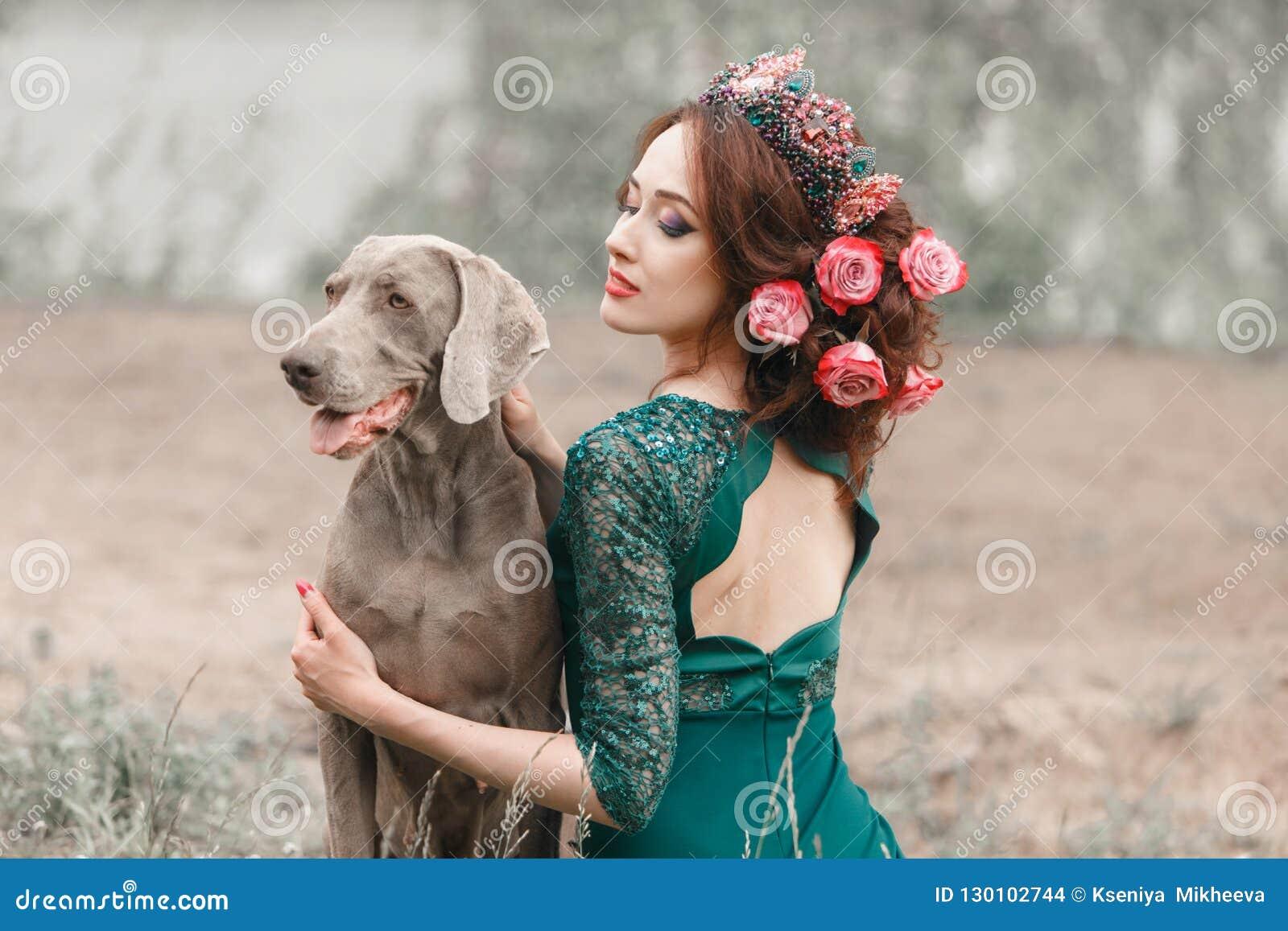 Όμορφο κορίτσι με τα λουλούδια που υφαίνονται στα αγκαλιάσματα Weimaraner τρίχας της