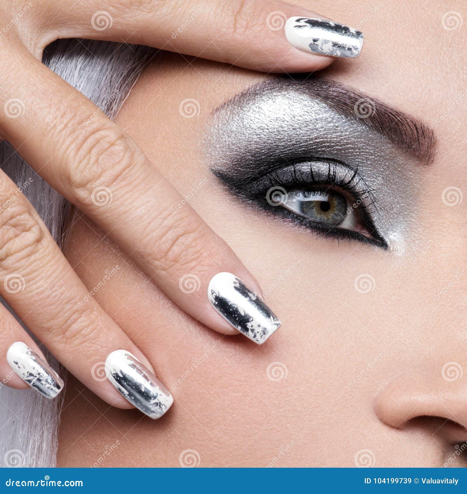 Όμορφο κορίτσι με το ασημένια makeup και τα καρφιά