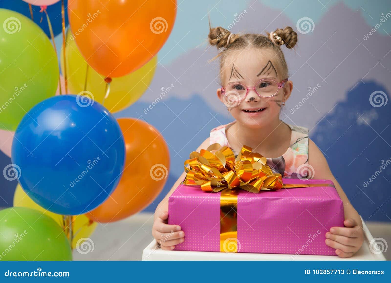 Όμορφο κορίτσι με το κάτω σύνδρομο με ένα παρόν γενεθλίων