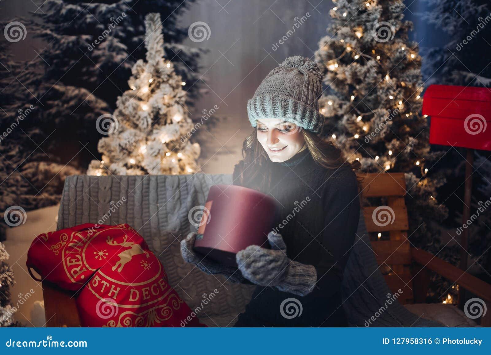 Όμορφο κορίτσι που ανοίγει το μαγικό κιβώτιο με το παρόν στη νύχτα Χριστουγέννων
