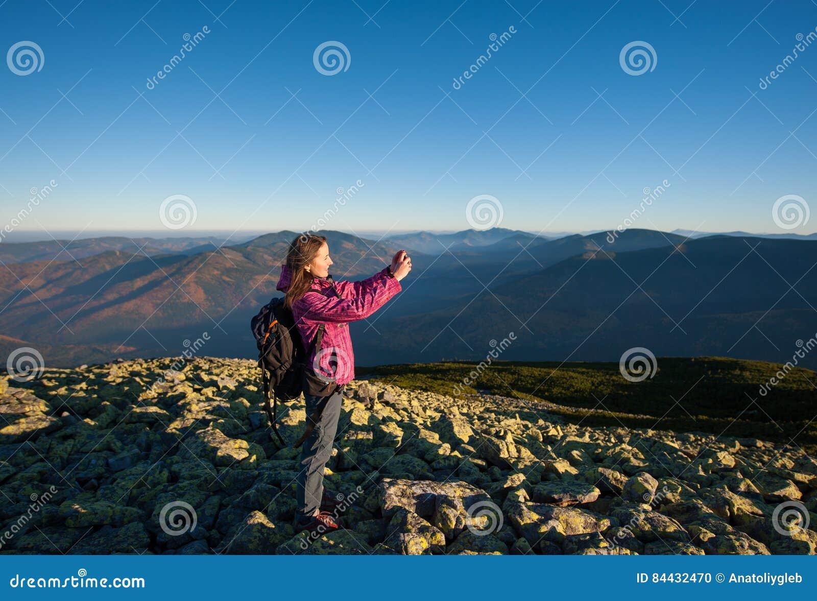 Όμορφο κορίτσι που παίρνει την εικόνα με το smartphone της στα βουνά