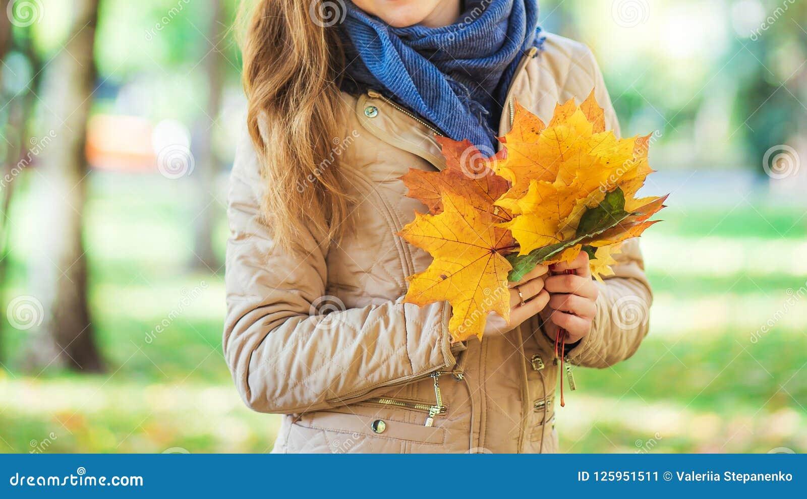 Όμορφο κορίτσι που περπατά στο πάρκο και που κρατά τα φύλλα φθινοπώρου