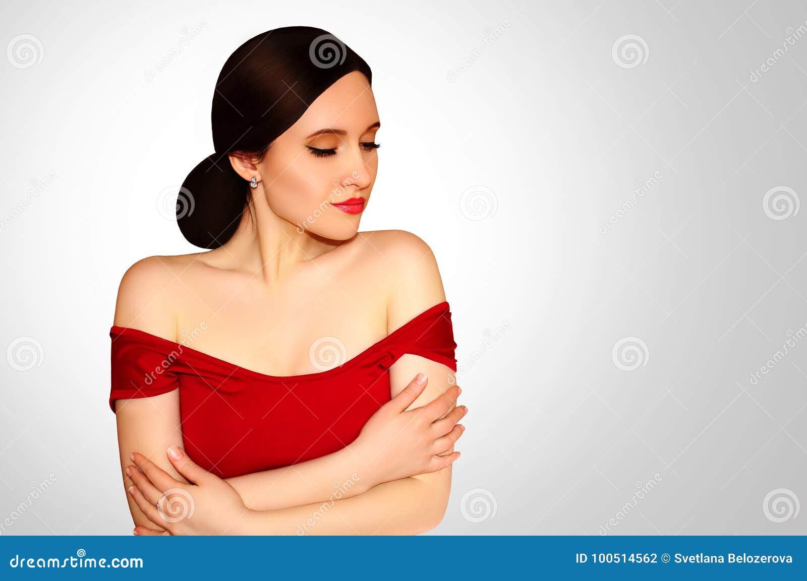 4afe42d93ad Όμορφο κορίτσι σε ένα κόκκινο φόρεμα με τους γυμνούς ώμους και κόκκινο  κραγιόν στο ανοικτό γκρι υπόβαθρο