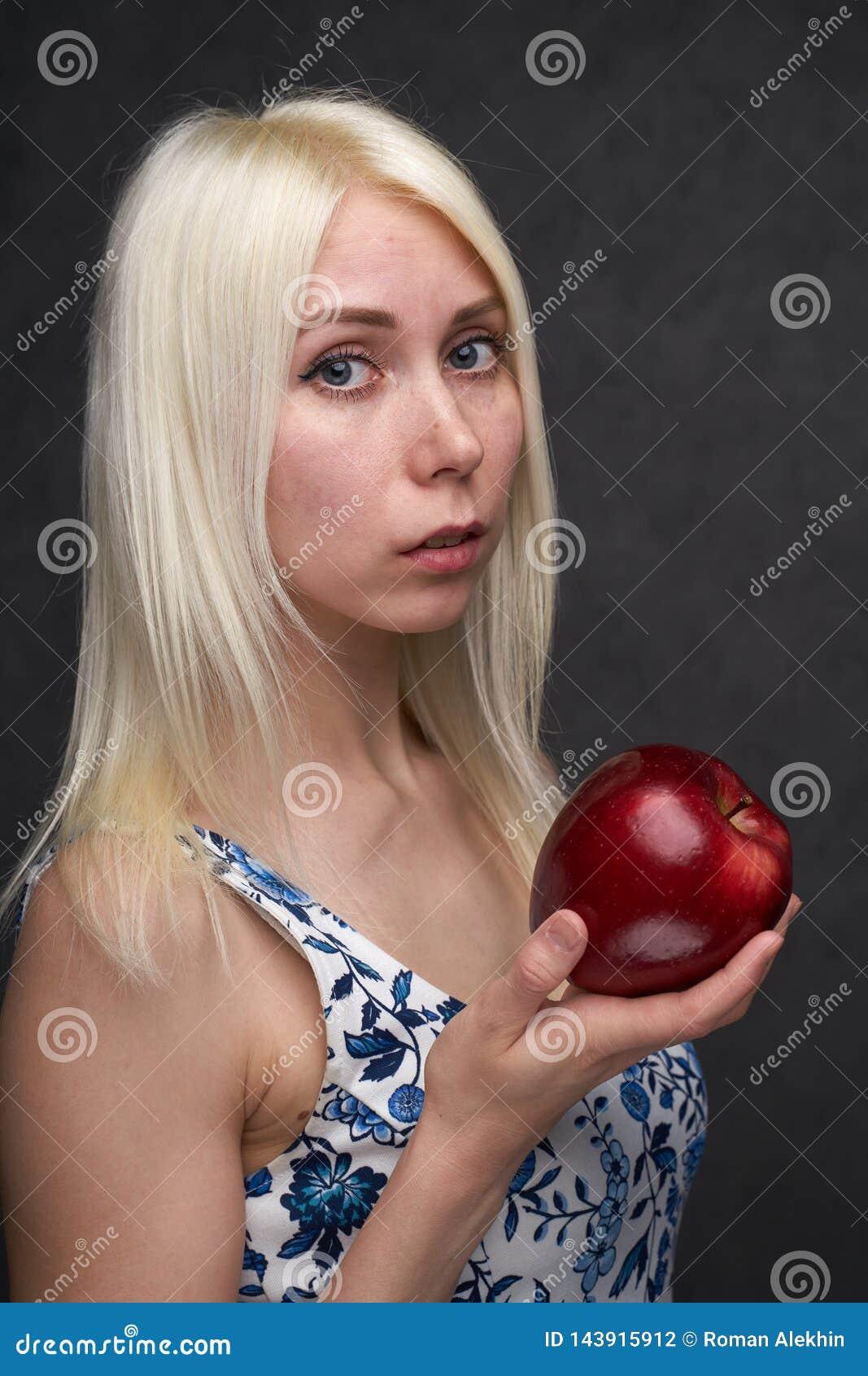 Όμορφο κορίτσι σε ένα μοντέρνο φόρεμα με το μήλο
