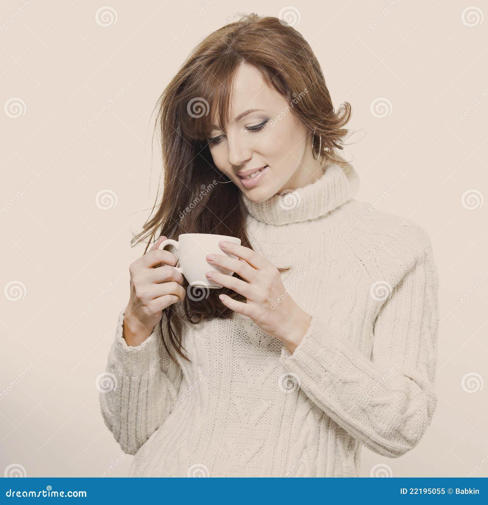 Όμορφο κορίτσι σε ένα πουλόβερ με ένα φλυτζάνι