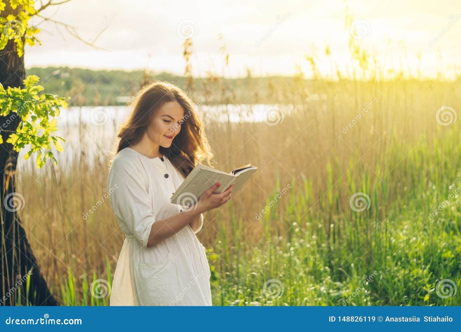 Όμορφο κορίτσι στον τομέα που διαβάζει ένα βιβλίο Η συνεδρίαση κοριτσιών σε μια χλόη, ανάγνωση ένα βιβλίο Υπόλοιπο και ανάγνωση