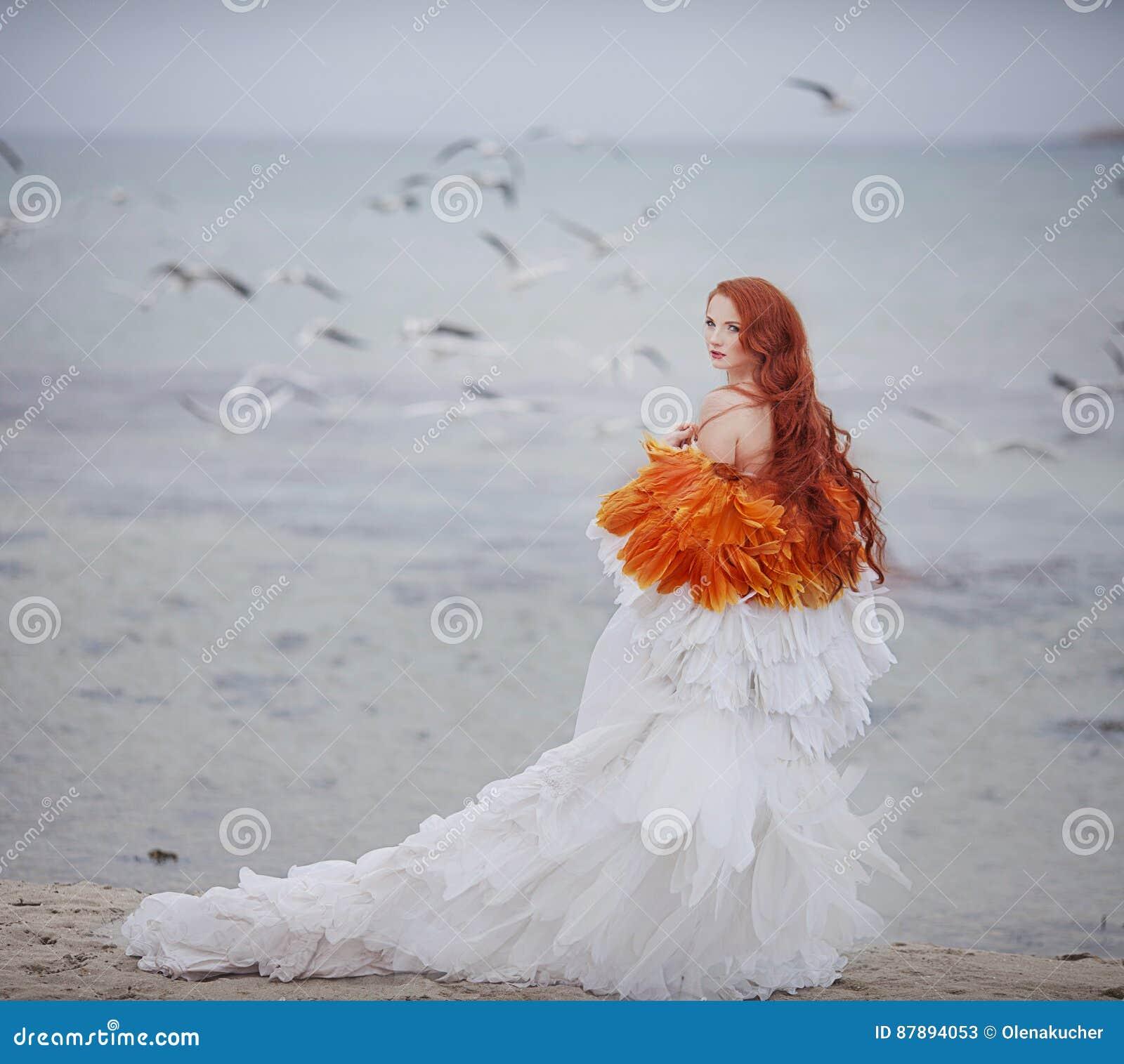 Όμορφο κορίτσι όπως έναν κύκνο στην παραλία