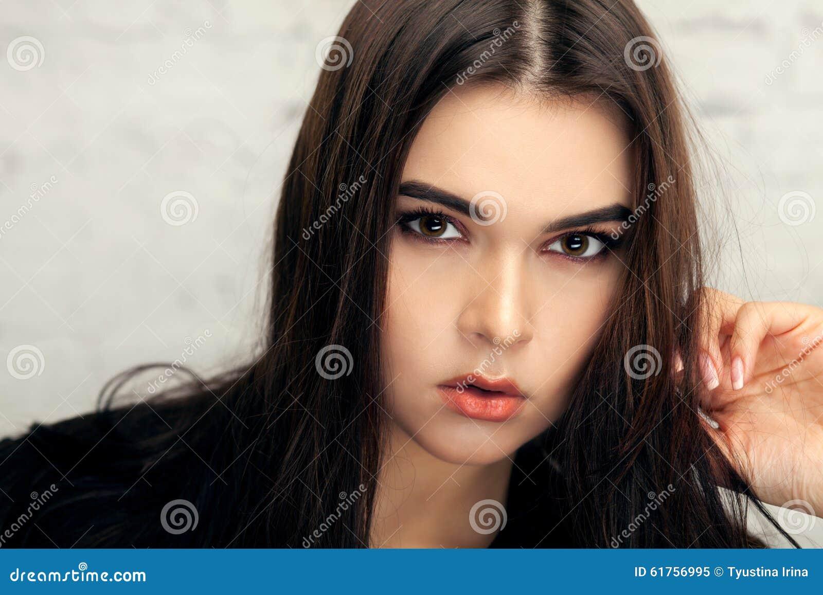 Όμορφο κορίτσι brunette με κατσαρωμένη την τρίχα ουρά