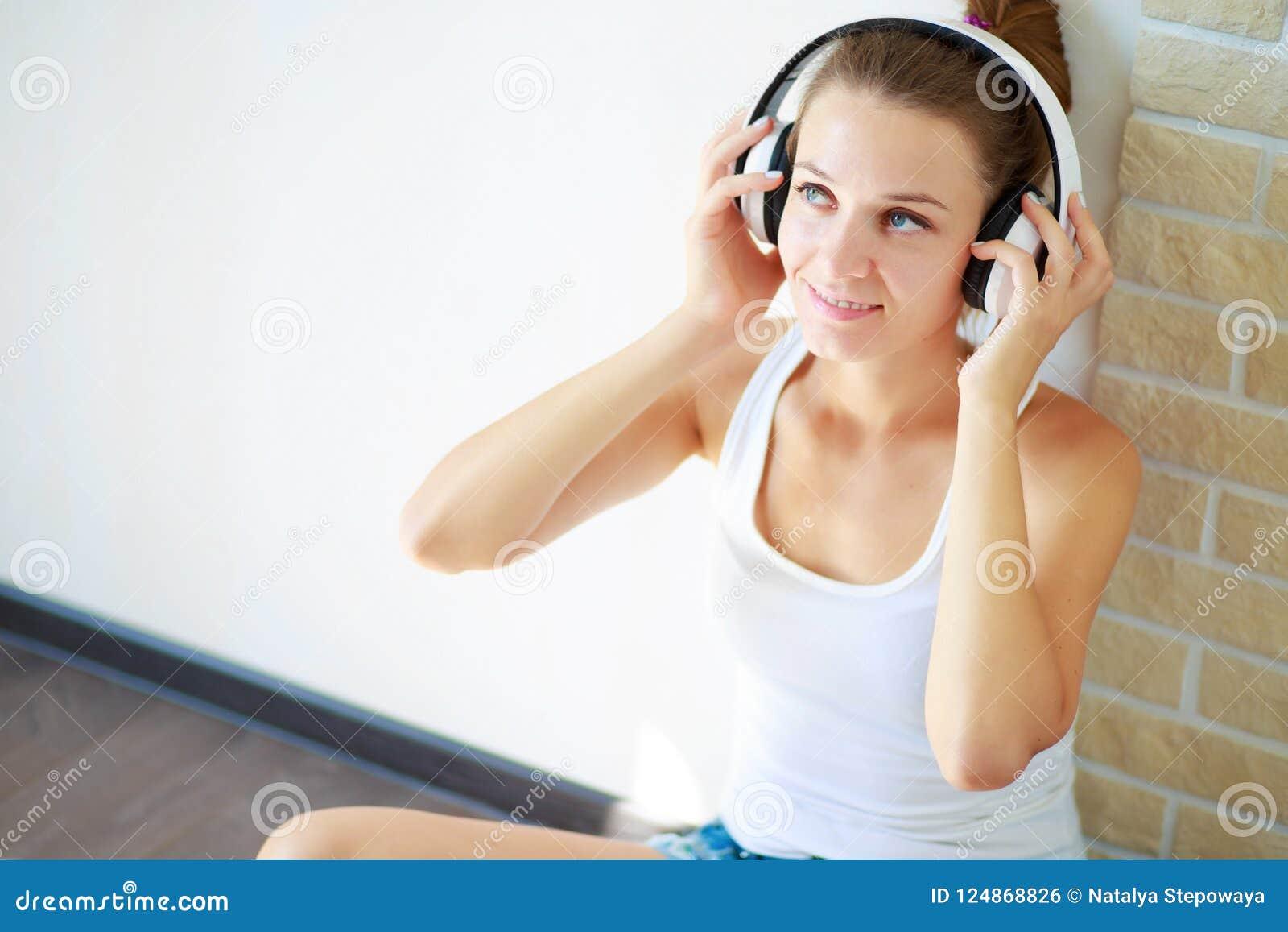 Όμορφο κορίτσι brunette με τα ακουστικά που ακούει τη μουσική καθμένος στο πάτωμα σε ένα κενό δωμάτιο στον άσπρο τοίχο