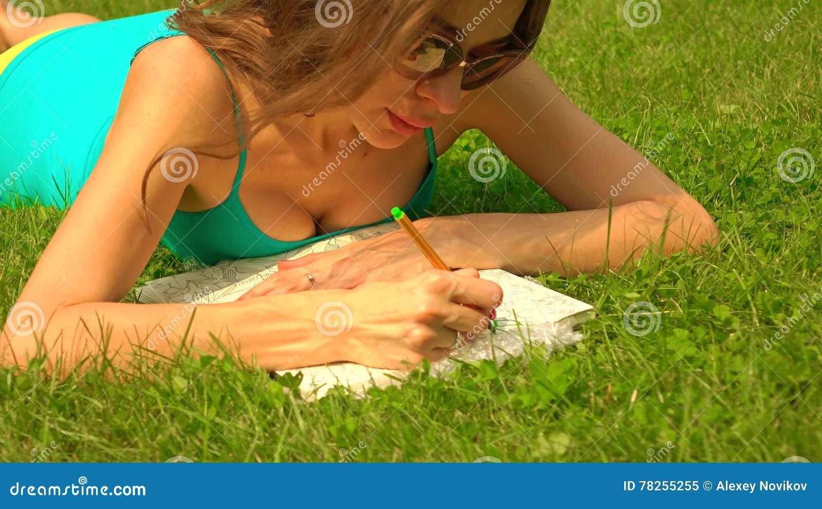 Όμορφο κορίτσι brunette στα γυαλιά ηλίου που βάζει στη χλόη και