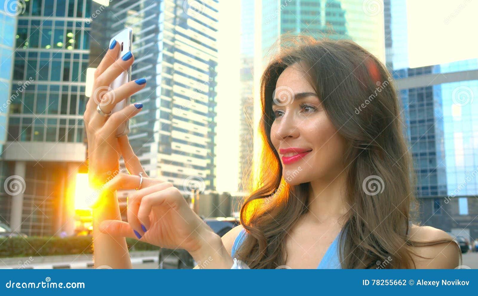 Όμορφο κορίτσι brunette στο μπλε φόρεμα που κάνει selfie στο ηλιοβασίλεμα ενάντια στους ουρανοξύστες