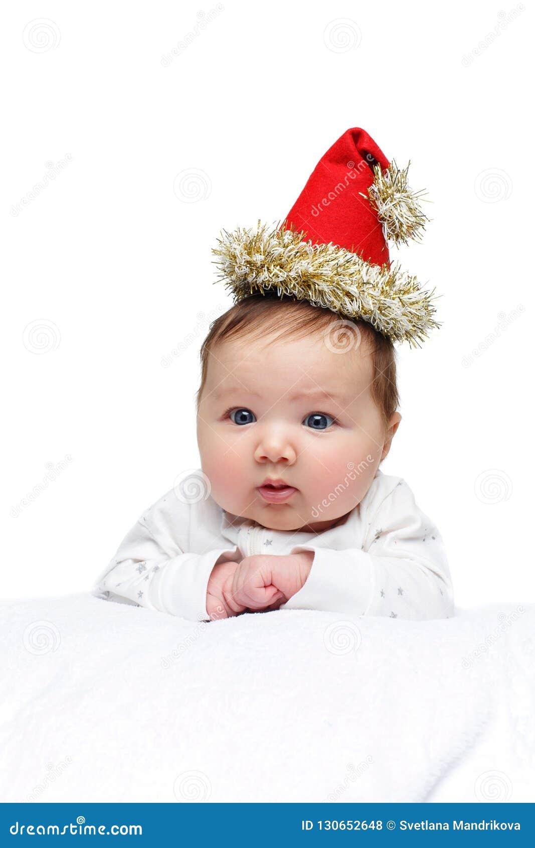 Όμορφο κοριτσάκι στο καπέλο Χριστουγέννων στο άσπρο κάλυμμα