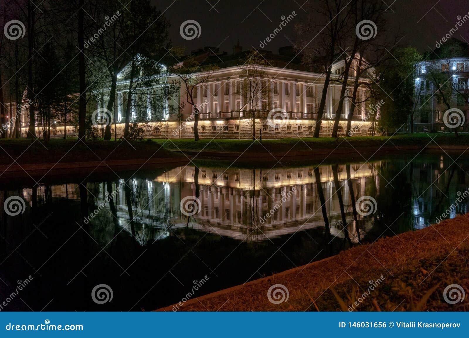 Όμορφο κτήριο που φωτίζεται από τα φω τα που απεικονίζονται στον ποταμό