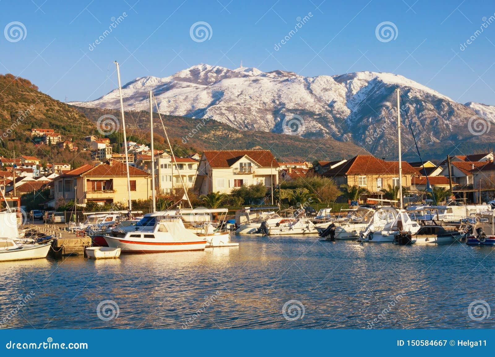 Όμορφο μεσογειακό τοπίο την ηλιόλουστη χειμερινή ημέρα Αλιευτικά σκάφη στο λιμάνι στο πόδι των χιονωδών βουνών Μαυροβούνιο, Tivat