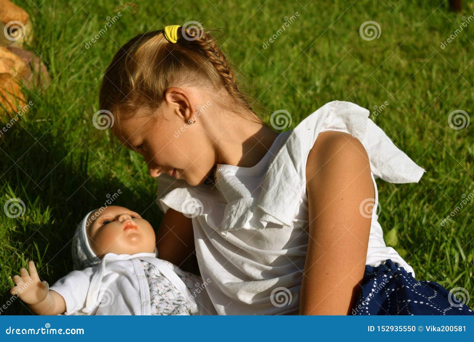 Όμορφο μικρό κορίτσι με μια κούκλα το καλοκαίρι σε έναν κήπο