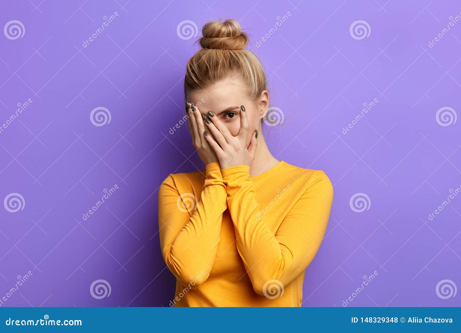 Όμορφο μοντέρνο κορίτσι που κρύβεται πίσω από τους φοίνικες