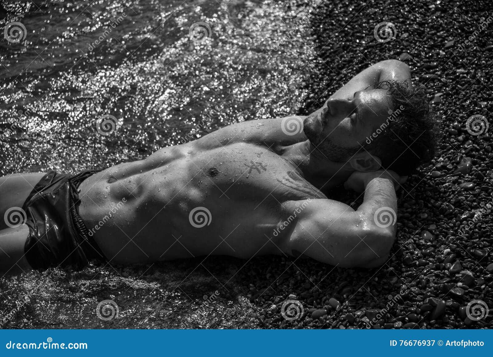 Όμορφο μυϊκό άτομο στην παραλία που βάζει στο αμμοχάλικο